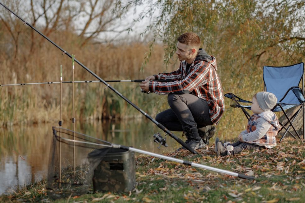 father-with-little-son-near-river-fishing-morning