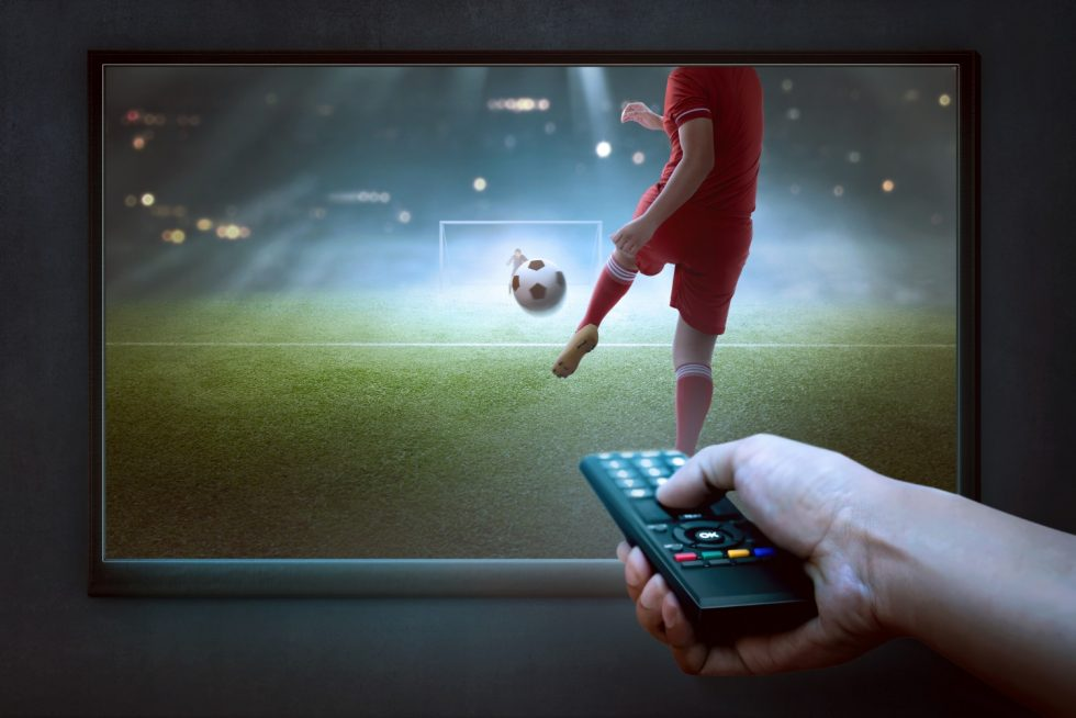 people-hands-with-remote-watching-football-game