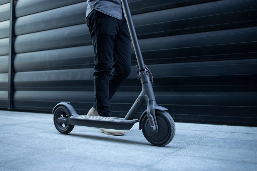 person-walking-by-his-electric-scooter