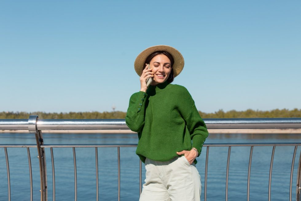 stylish-woman-green-casual-sweater-hat-outdoor-bridge-with-river-view-warm-sunny-summer-day-talks-mobile-phone