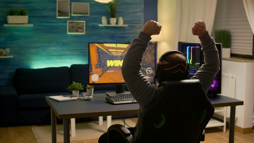 videogamer-player-raising-hands-after-winning-first-person-shooter-competition-wearing-hradphones-professional-pro-gamer-playing-online-video-games-with-new-graphics-powerful-computer
