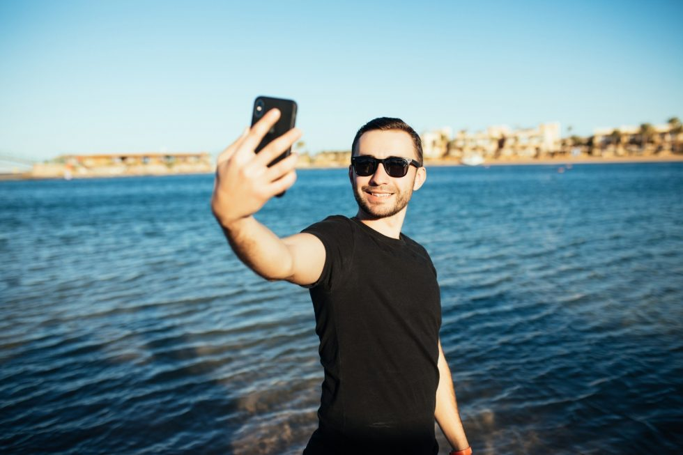 young-handsome-man-doing-self-portrait-with-smartphone-beach