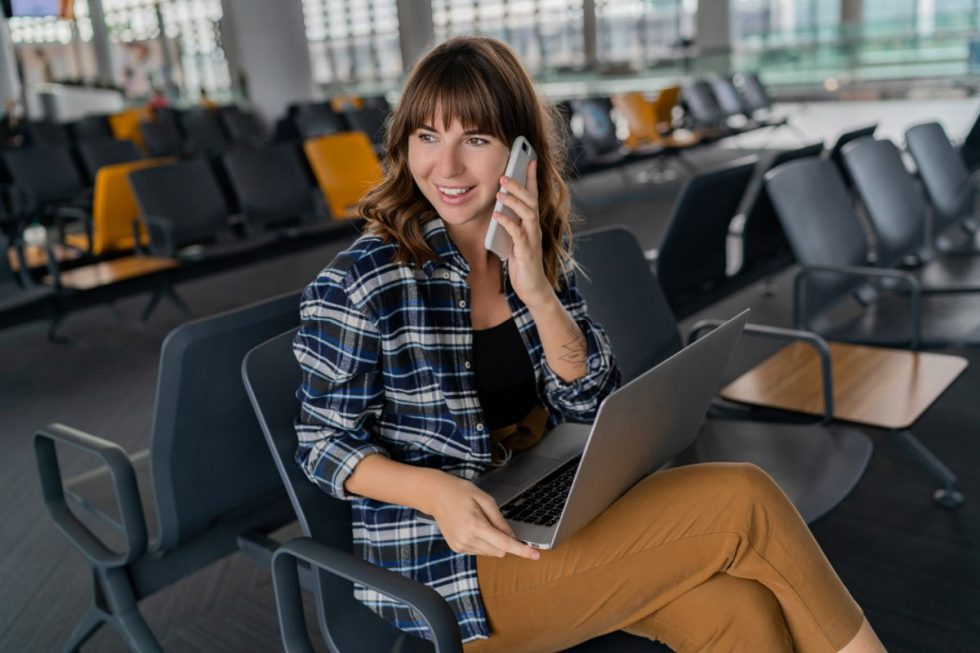 airport-young-female-passenger-with-smart-phone-laptop-sitting-terminal-hall-while-waiting-her-flight